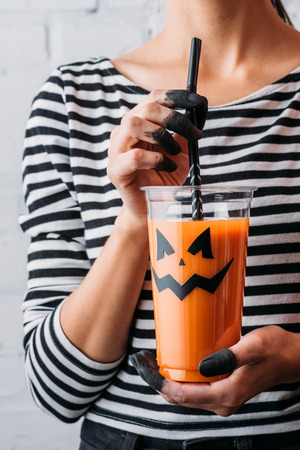 cropped shot of woman holding glass of pumpkin juice with jacks face, halloween concept