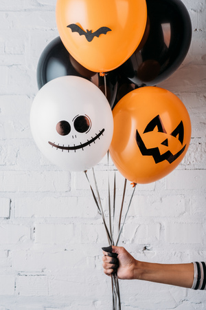 cropped shot of woman holding various halloween balloons