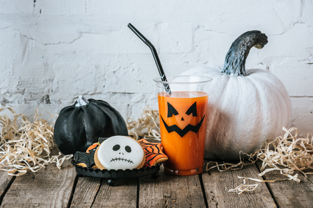 close-up shot of halloween composition with pumpkins, cookies and glass of pumpkin juice
