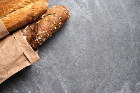 top view of baguettes in paper bag on grey surface 스톡 콘텐츠 - 110595683