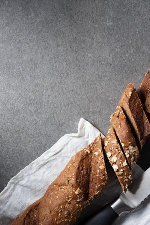top view of cut baguette in white linen on grey tabletop Foto de archivo - 110595713