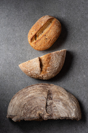 flat lay with halves of bread on grey surface Foto de archivo