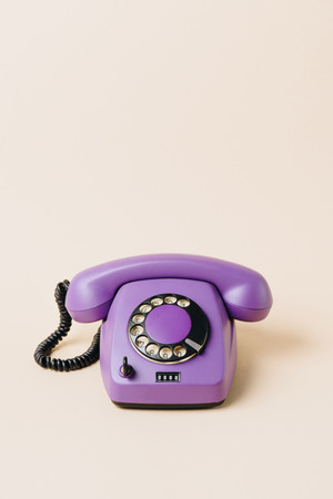 one purple vintage telephone on beige Stock Photo