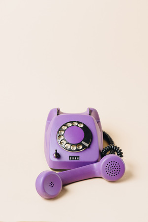 purple vintage rotary telephone with tube on beige