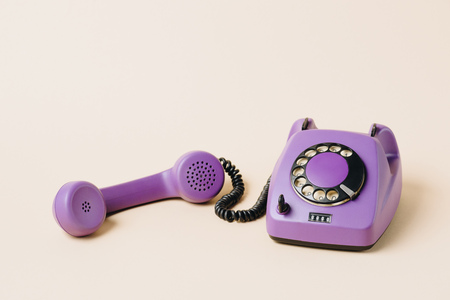 purple retro rotary phone with tube on beige