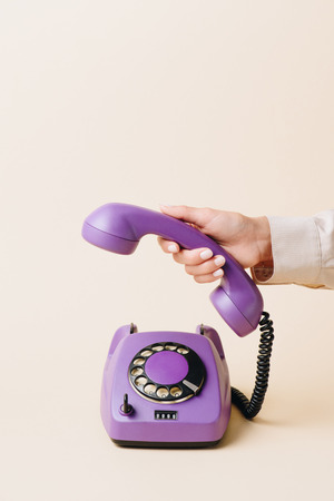 cropped view of woman holding phone tube of purple rotary phone on beige Stock Photo