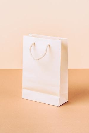 bolsa de papel blanco sobre beige Foto de archivo