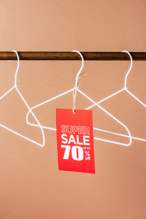 hangers with red super sale tag - 70 percents discount on beige 스톡 콘텐츠
