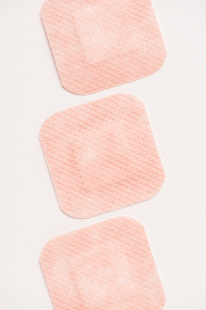 top view of row of adhesive bandages on white surface