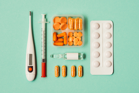 top view of thermometer, syringe, ampoule with medicine, blister pack and pills on green Reklamní fotografie