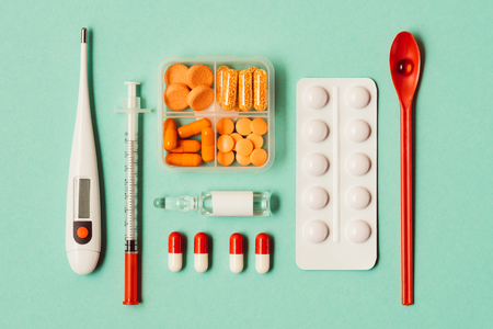 top view of various medicines, syringe and thermometer on green Reklamní fotografie