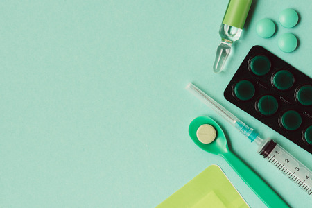 top view of ampoule with medicine, blister pack, pills and syringe on green background