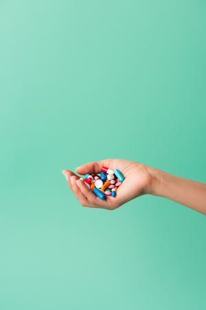 cropped shot of person holding various colorful pills isolated on green 写真素材 - 110669006