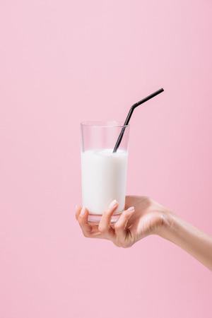 abgeschnittene Aufnahme einer Frau mit einem Glas Milch isoliert auf rosa