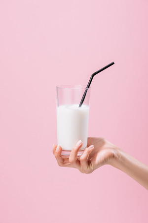 Captura recortada de mujer sosteniendo un vaso de leche aislado en rosa