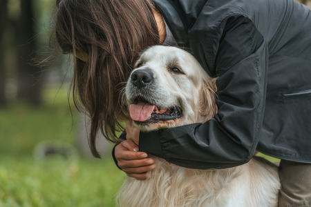 young woman hugging cute funny dog in park Stockfoto