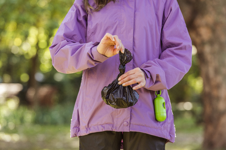 cropped shot of young woman holding trash bag while cleaning after pet in park Banque d'images - 110669875