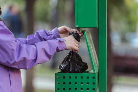 cropped shot of woman putting bag in trash can in park, cleaning after pet concept Banque d'images - 110669877