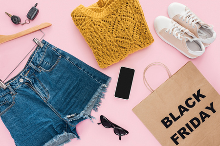 top view of stylish clothes, smartphone, car key and shopping bag with black friday sign Stok Fotoğraf