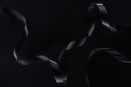 top view of black glossy ribbon on black background Banque d'images - 110670703