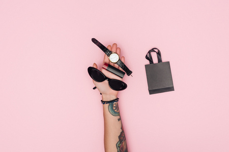 partial view of tattooed girl holding accessories near little shopping bag isolated on pink Banque d'images - 110670922