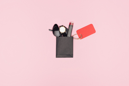 top view of little shopping bag with lipstick, accessories and empty sale tag isolated on pink Banque d'images - 110670934