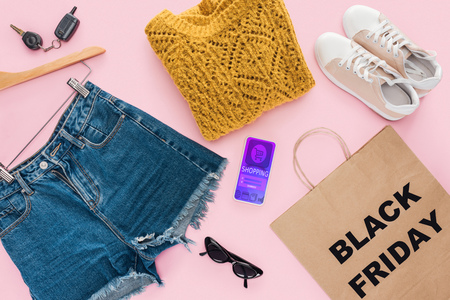 top view of trendy clothes, smartphone with shopping app and paper bag with black friday sign Banque d'images - 110671058