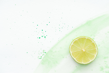 top view of piece of ripe lime on white surface with green watercolor