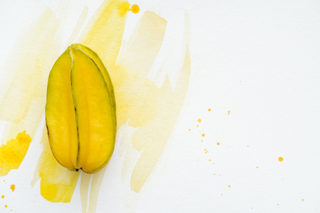 top view of yummy sweet carambola on white surface with yellow watercolor