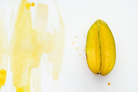 top view of tasty exotic carambola on white surface with yellow watercolor