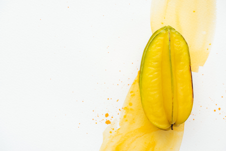 top view of one ripe carambola on white surface with yellow watercolor