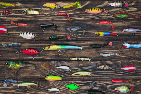 flat lay with arranged various fishing bait on wooden background