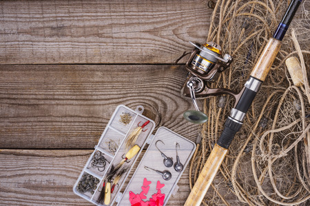 flat lay with fishing net, fishing rod and plastic box with fishing tackle and hooks on wooden planks Archivio Fotografico