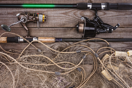 top view of fishing rods and fishing net on wooden planks