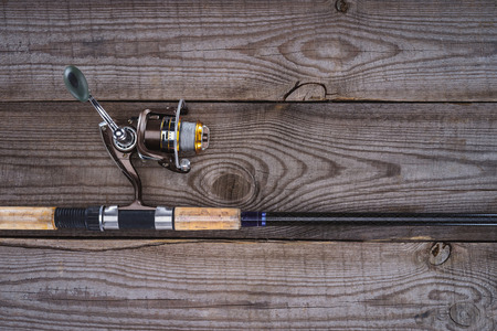 elevated view of fishing rod on wooden planks, minimalistic concept