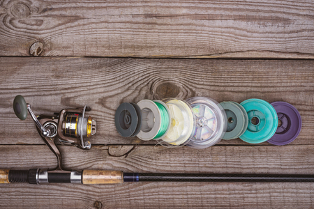 top view of fishing rod and various reels on wooden planks Stok Fotoğraf