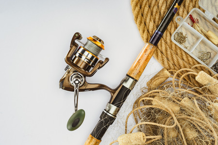 top view of fishing rod, nautical rope and plastic box with fishing tackle and bait isolated on white Stock Photo
