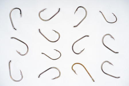 top view of arranged fishing hooks isolated on white