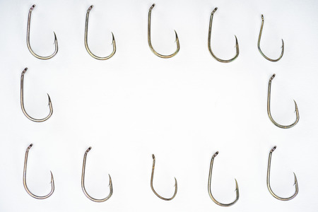 elevated view of arranged fishing hooks isolated on white