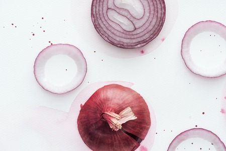 top view of sliced spicy red onion on white surface with pink watercolor blot