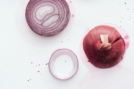 top view of raw whole red onion with slice on white surface with pink watercolor blots
