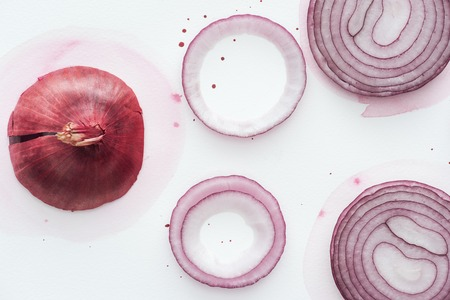 top view of red onion with slices and rings on white surface with pink watercolor blots Stock Photo