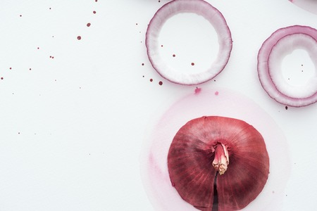 top view of whole red onion with rings on white surface with pink watercolor blots