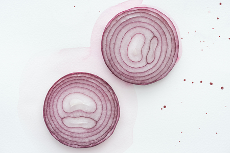 top view of two slices of red onion on white surface with pink watercolor blots
