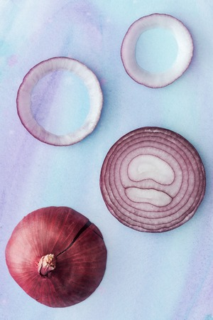 top view of raw sliced red onion on white surface with blue watercolor strokes