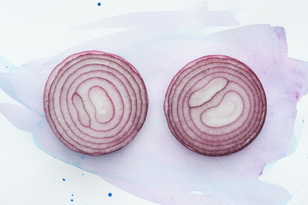 top view of two slices of red onion on white surface with purple watercolor strokes Stock Photo