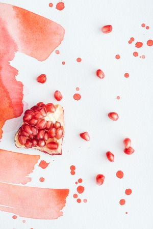 top view of ripe pomegranate on white surface with red watercolor strokes