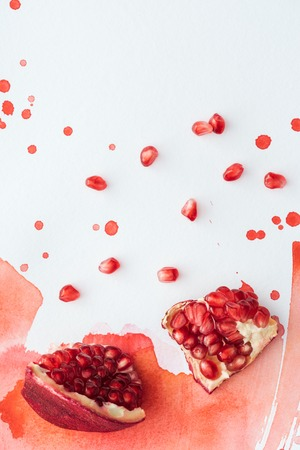 top view of delicious pomegranate on white surface with red watercolor strokes