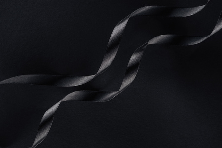 top view of two glossy ribbons on black background