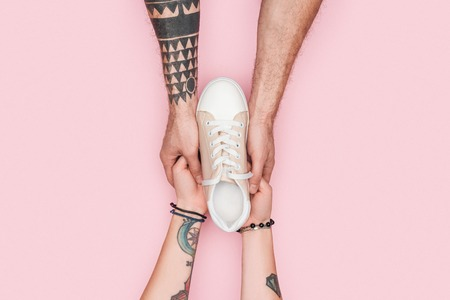 cropped view of tattooed couple holding one sneaker isolated on pink Banque d'images - 110700636